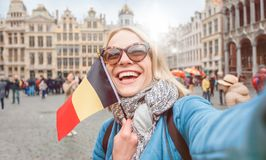 Woman tourist stands with the flag of Belgium on the background of the Grand-Place or the Grand Market Square in royalty free stock photography