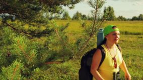 A woman tourist stands in a forest glade and looks through binoculars where to go next. The average plan stock footage