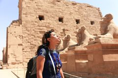 Woman Tourist stroll in ram-headed sphinxes at Karnak Temple Luxor royalty free stock photography