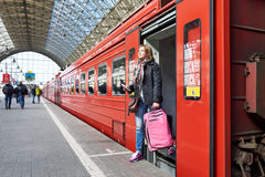 Woman tourist with suitcase coming out of train at station Royalty Free Stock Photo