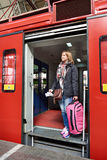 Woman tourist with suitcase coming out of train at station Royalty Free Stock Image