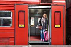 Woman tourist with suitcase coming out of train at station Stock Images