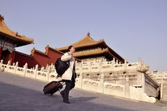 A woman tourist with suitcase at Forbidden City, China royalty free stock images