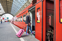 Woman tourist with suitcase sits on train at railway station Stock Photos