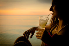 Woman tourist in summer vacation drinking cocktail at sunset Stock Photography