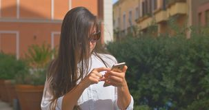 Woman tourist in sunglasses is looking for an address with a GPS navigator on a smartphone