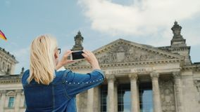 A woman tourist takes pictures of the building of the Bundestag in Berlin. Tourism in Germany and Europe concept. 4K video stock footage