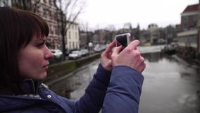 Woman tourist takes pictureson on smartphone in Amsterdam. Woman tourist takes pictureson on smartphone in Amsterdam stock video footage