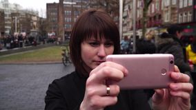 Woman tourist takes pictureson on smartphone the city. Amsterdam Rembrandtplein . slow motion. Woman tourist takes pictureson on smartphone the city. Amsterdam stock video