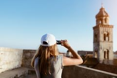 Woman tourist taking photo of old church. With her smartphone. Dubrovnik, Croatia Stock Image