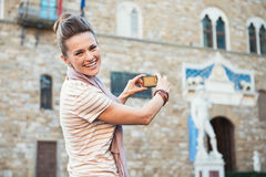 Woman tourist taking photo of Palazzo Vecchio in Florence, Italy Stock Photos