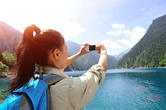 Woman tourist taking photo with smart phone Stock Photos
