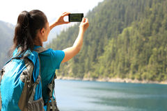 Woman tourist taking photo with smart phone Stock Images