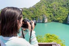Woman tourist taking photos Blue Lagoon. Woman tourist at Thale Nai on Koh Mae Ko island viewpoint use camera taking photos at beautiful nature landscape of Blue Stock Image