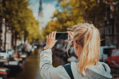 Woman tourist taking a picture of canal in Amsterdam on the mobile phone. Warm gold afternoon sunlight. Travel in Europe.  stock photo