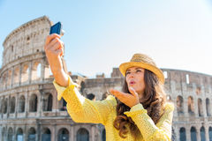 Woman tourist taking selfie blowing kisses at Rome Colosseum Royalty Free Stock Image