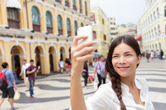 Woman tourist taking selfie pictures in Macau. China in Senado Square or Senate Square. Asian girl tourist using smart phone camera to take photo while Royalty Free Stock Photos