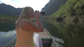 Woman tourist taking shots of Trang An nature, Vietnam. Woman tourist traveling by boat in Trang An and taking photos of beautiful mountain landscape with stock video footage