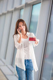 Woman tourist talking by cell phone with boarding Royalty Free Stock Photos