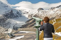 Woman tourist with telescope in Grossglockner, High Alps, Austria. Stock Images