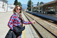 Woman tourist thumbs up on railroad station Royalty Free Stock Photos