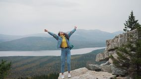 Woman tourist on top is happy and celebrating success. A woman in a denim jacket on top of the world rejoices in a. Victorious gesture stock video
