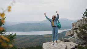Woman tourist on top is happy and celebrating success. A woman in a denim jacket on top of the world rejoices in a. Victorious gesture stock footage