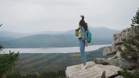 Woman tourist on top is happy and celebrating success. A woman in a denim jacket on top of the world rejoices in a. Victorious gesture stock video footage