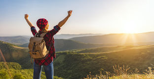 Woman tourist at top of mountain at sunset outdoors during  hike Stock Image