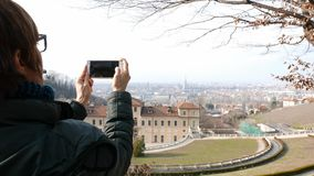 Woman tourist using smart phone, taking picture to urban panorama at Turin, Torino travel destination in Italy. Woman tourist using smart phone, taking picture stock video
