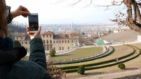 Woman tourist using smart phone, taking picture to urban panorama at Turin, Torino travel destination in Italy.