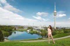 Woman tourist visiting landmark Olympiapark with Olympic tower a. T Munich, Bavaria, Germany.  Green park at city Stock Image