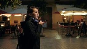 Woman tourist voice recognition ai sending audio message on cellphone phone at night city street speech helper commander