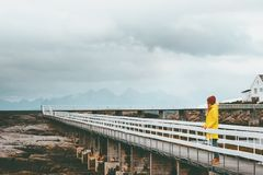 Woman tourist walking alone on bridge Travel Lifestyle emotional concept vacations outdoor yellow raincoat clothing foggy mountain. S on background Royalty Free Stock Photography