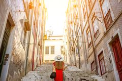 Woman traveling in Lisbon, Portugal. Woman tourist walking back on the narrow street in Alfama region during the morning light in Lisbon, Portugal stock photography
