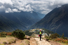 Woman tourist walking mountain trail above Namche Bazaar village Royalty Free Stock Images