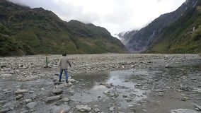 Woman tourist walking in trail of fox glacier new zealand stock footage