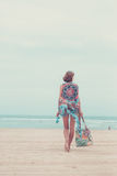 Woman tourist walking on a tropical summer vacation beach wearing sunglasses and beach bag relaxing on travel holidays Royalty Free Stock Image