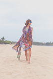 Woman tourist walking on a tropical summer vacation beach wearing sunglasses and beach bag relaxing on travel holidays Royalty Free Stock Images