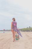 Woman tourist walking on a tropical summer vacation beach wearing sunglasses and beach bag relaxing on travel holidays Royalty Free Stock Photos