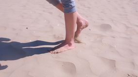Woman tourist walks barefooted on sand at sea beach resting on vacation. stock video