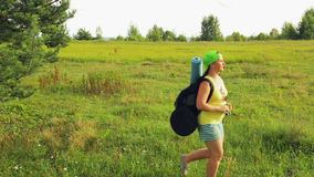 A woman tourist walks through a forest glade and looks through binoculars where to go next. Overall plan stock video footage