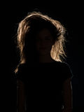 Woman with tousled hair in black shadow. Front view of woman with tousled hair in black shadow, n black background Royalty Free Stock Photos