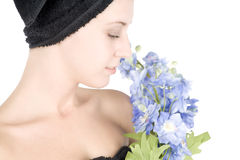 Woman with towel around hair holding flowers Stock Images