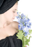 Woman with towel around hair holding flowers Royalty Free Stock Photo