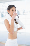 Woman with towel around neck drinking water Royalty Free Stock Photos