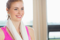Woman with towel around neck listening to music in fitness studio Royalty Free Stock Image