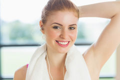 Woman with towel around neck listening to music in fitness studio Stock Image