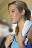 Woman With Towel Around Neck Looking Away At Gym Stock Photo