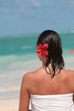 Woman in towel on the beach. Woman in white towel with brown hairs and red flower standing on the beach Royalty Free Stock Photo